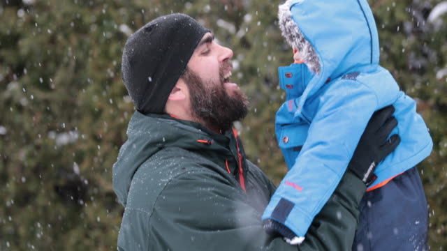 Father and Son Playing Outdoor in Winter Snowstorm