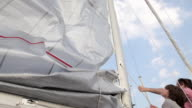 Father and son raising sail on yacht