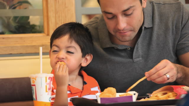 CU Father and son (2-3) sharing meal at fast food restaurant / Richmond, Virginia, USA