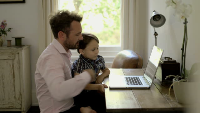 Father and son sitting at table using laptop.