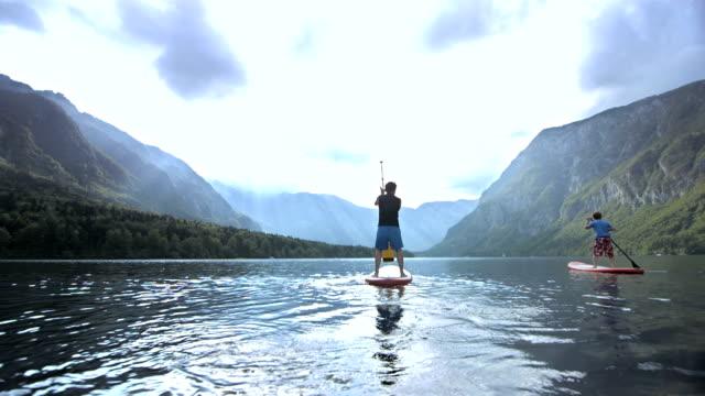 Vater und Sohn SUPing auf den See