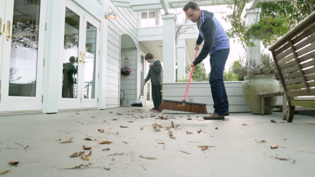 Father and son sweeping leaves on porch