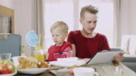 DS WS Father and son using a digital tablet while having breakfast