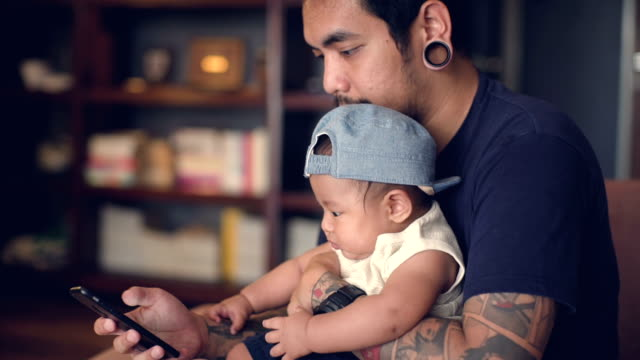 Father and son using smart phone at home