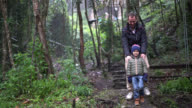 Father and son walking carefully in the woods