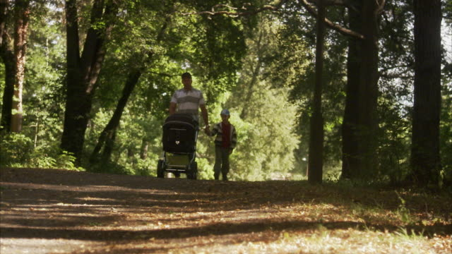 Father and son walking in a park a sunny day Sweden.