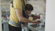 Father and son washing dishes in kitchen sink