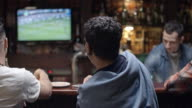 Father and son watching soccer in pub