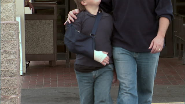 SLO MO, MS, TU, Father and son (8-9) with arm in sling leaving hospital, Oroville, California, USA