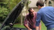 MS PAN R/F Father and teenage boy (16-17) working on engine of  car / Neenah, Wisconsin, USA