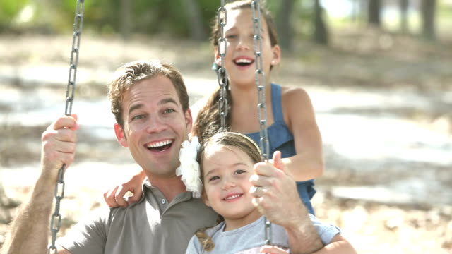 Father and two daughters at the park on tire swing
