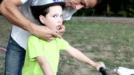 Vater Unterstützung Kind mit Fahrradhelm.