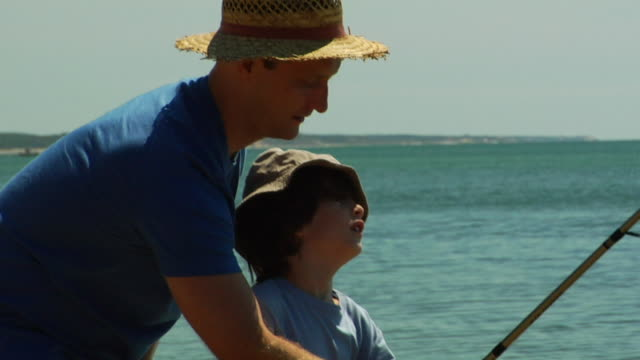 CU, TU, Father assisting son (6-7) fishing in ocean, North Truro, Massachusetts, USA
