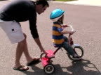 MS, TS, Father assisting son (2-3) with tricycle on street, Simi Valley, California, USA