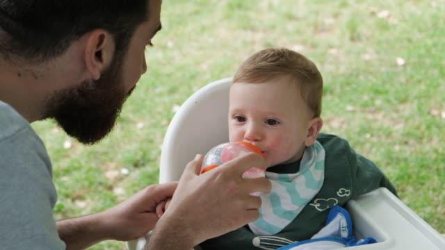 Father bottle feeds baby boy outdoors.