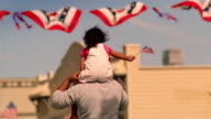 Father carrying daughter on his shoulders / girl waves American flag / California