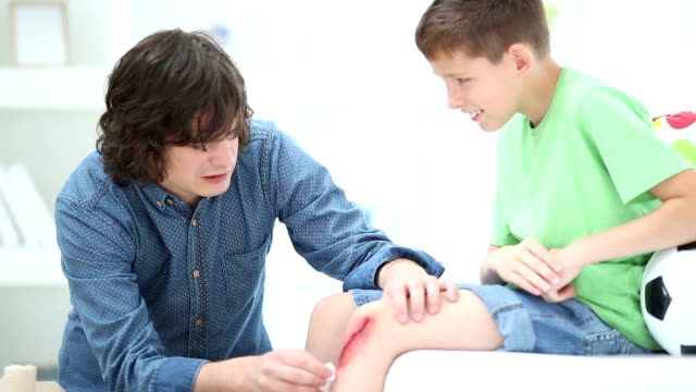 HD: Father Cleaning Wound on Childs Knee.
