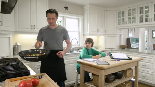 Father cooking and helping his son with homework