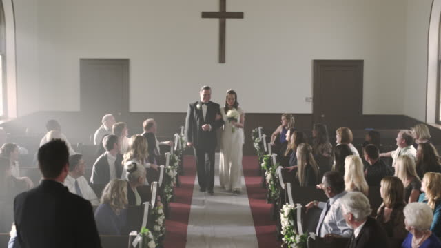 Father escorting bride to the groom in a chapel.