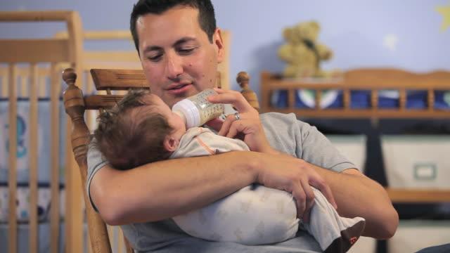 CU Father feeding baby boy (2-5 months) from bottle in nursery room / Richmond, Virginia, USA.
