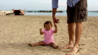 Father helping baby to make first steps