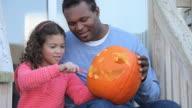 MS TU Father helping daughter (6-7) carving jack o' lantern on porch / Richmond, Virginia, USA