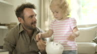Father helping daughter to save money in piggy bank.