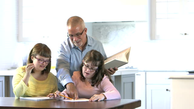 Father helping down syndrome girls with homework