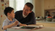 MS Father helping son with homework in kitchen / China
