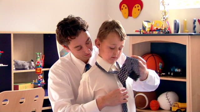 Father helping son with necktie