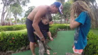 Father helps son with golf swing and son gets upset and leaves and sister watches.