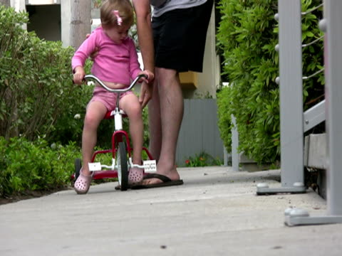 Vater hilft/lehrt Kinder lernen, mit dem Fahrrad