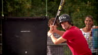 Father hitting balls in batting cage as son and wife watch outside cage