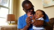 MS ZI ZO Father holding infant son on lap playing clapping game