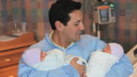 MS father holding newborn twins looking at camera and smiling / Richmond, Virginia, USA