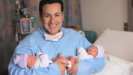 MS PORTRAIT father holding newborn twins looking up and smiling / Richmond, Virginia, USA