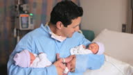 TU MS PORTRAIT father holding newborn twins looking up and smiling / Richmond, Virginia, USA