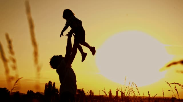 SLO MO Father lifting his son up in the air