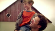 Father lifting son onto shoulder in front of barn / talking / son lying across father's shoulders