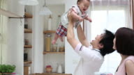 A father lifts his baby up high and his wife watch them with pleasure in kitchen