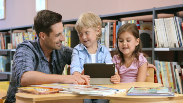 DS vader kijken naar zijn kinderen met behulp van een tablet in de bibliotheek