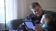 MS Father playing with a digital tablet with his daughter