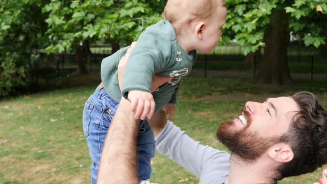 Father playing with baby son lifting him in air, mum is looking on.