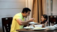 Father playing with her daughter at dinning table, Delhi, India