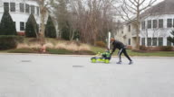 Father pushes boy in gocart up a residential street.