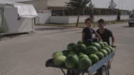 Father pushes watermelon cart in Kilis Oncupinar Accommodation Facility in Turkey which is a model refugee camp for Syrian refugees
