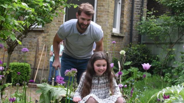 Father pushing daughter in wheelbarrow in garden