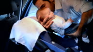 Father puts baby daughter in car seat, side view