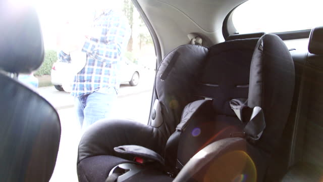 Vater Setzen Tochter im Kindersitz im Auto-Reise