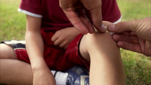 A father putting on a plaster on the knee of his son Sweden.